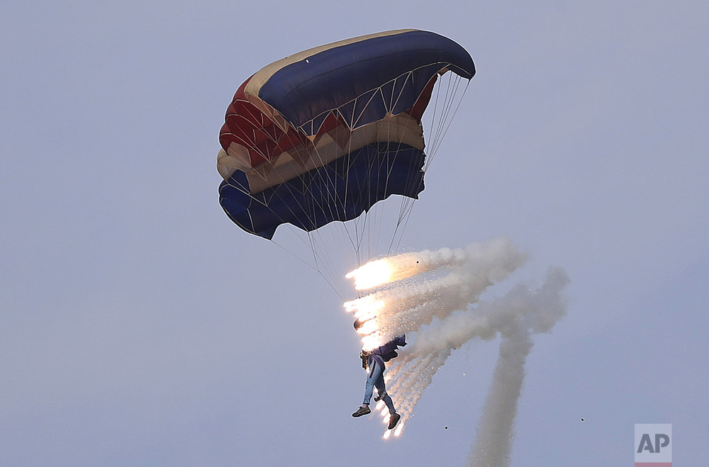 Pyrotechnics explode as a military parachutist descends upon Kalma Airport in Wonsan, North Korea, on Sept. 25, 2016. Thousands of Koreans and hundreds of foreign tourists and journalists invited to Wonsan, a port city, for the Wonsan International Friendship Air Festival, were given a glimpse of North Korea's own Air Force fighters, remote-controlled scale mock-up planes including an F-16 fighter jet, and demonstrations of military parachuting, with the first two skydivers descending with huge North Korean and ruling party flags. (AP Photo/Wong Maye-E)