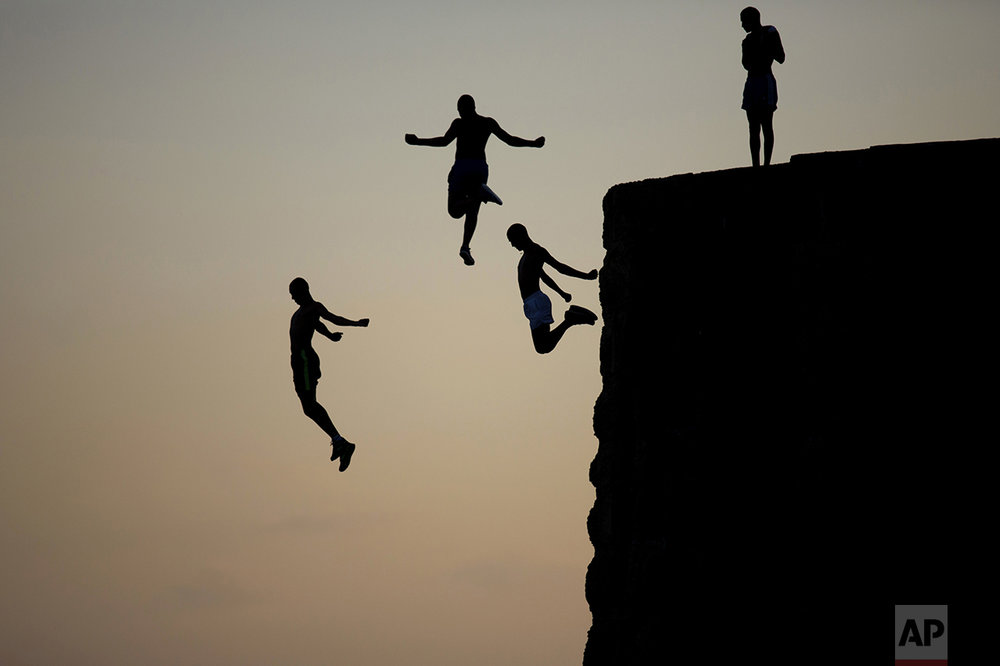 Israeli Arab boys jump into the Mediterranean sea from the ancient wall surrounding the old city of Acre, northern Israel, on Aug. 2, 2016. (AP Photo/Ariel Schalit)