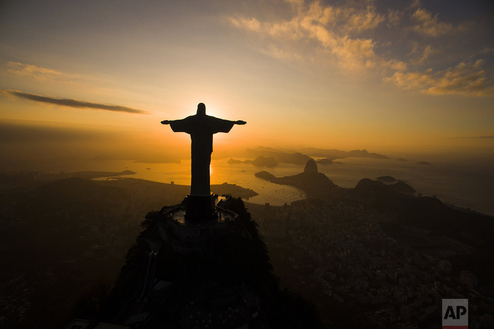The sun rises behind the Christ the Redeemer statue, above the Guanabara bay in Rio de Janeiro, Brazil, on July 19, 2016, ahead of the 2016 summer Olympics. (AP Photo/Felipe Dana)