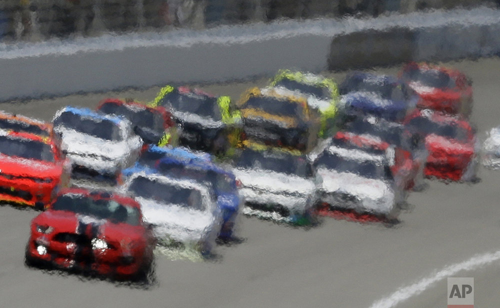 Heat waves distort this image of drivers following the pace car during the NASCAR Xfinity series auto race at Michigan International Speedway, on June 11, 2016, in Brooklyn, Mich. (AP Photo/Carlos Osorio)