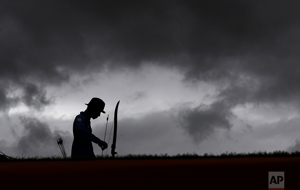 Taiwan's Guan-lin is silhouetted as he prepares to shoot during an elimination round of the individual archery competition at the Sambadrome venue during the 2016 Summer Olympics in Rio de Janeiro, Brazil, on Aug. 10, 2016. (AP Photo/Alessandra Tarantino)