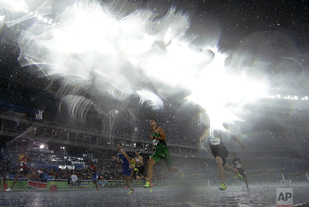 Hungary's Balazs Baji, center, and Canada's Johnathan Cabral compete in a men's 110-meter hurdles heat during heavy rain at the athletics competitions of the 2016 Summer Olympics at the Olympic stadium in Rio de Janeiro, Brazil, on Aug. 15, 2016. (AP Photo/Matt Slocum)