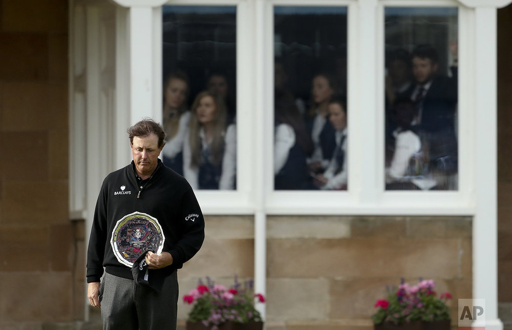 Phil Mickelson of the United States looks down as he holds the silver plate, for being runner up in the British Open Golf Championships at the Royal Troon Golf Club in Troon, Scotland, on July 17, 2016. Henrik Stenson won the Championship. (AP Photo/Peter Morrison)