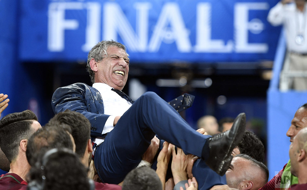 Portugal coach Fernando Santos is lifted by the players after winning the Euro 2016 final soccer match between Portugal and France at the Stade de France in Saint-Denis, north of Paris, on July 10, 2016. (AP Photo/Martin Meissner)