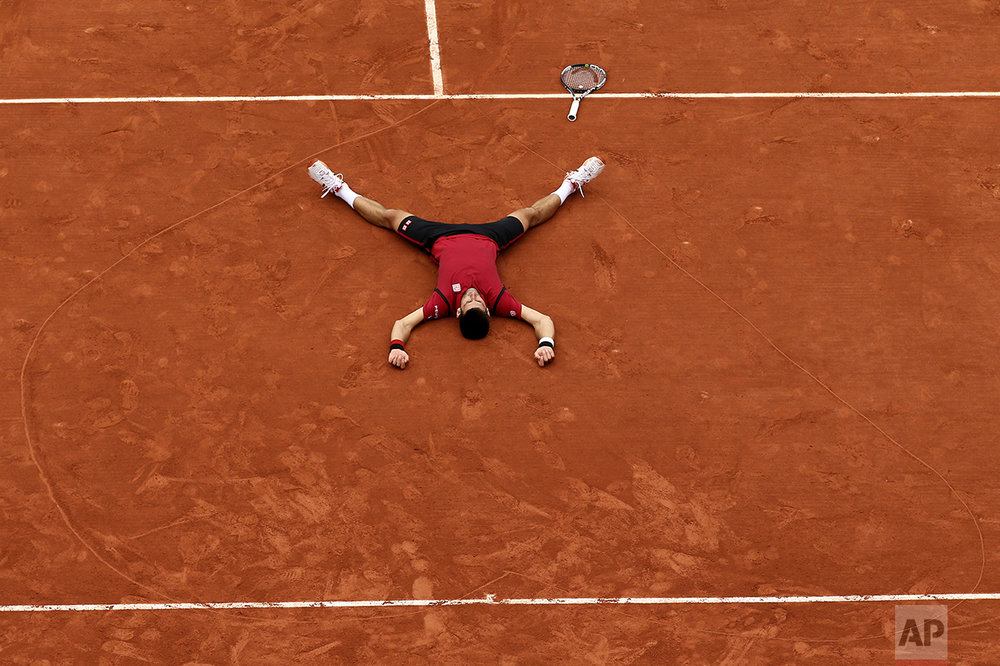 Serbia's Novak Djokovic lies on the clay in a heart he drew after defeating Britain's Andy Murray during their final match of the French Open tennis tournament at the Roland Garros stadium on June 5, 2016, in Paris. Djokovic won 3-6, 6-1, 6-2, 6-4. (AP Photo/David Vincent)