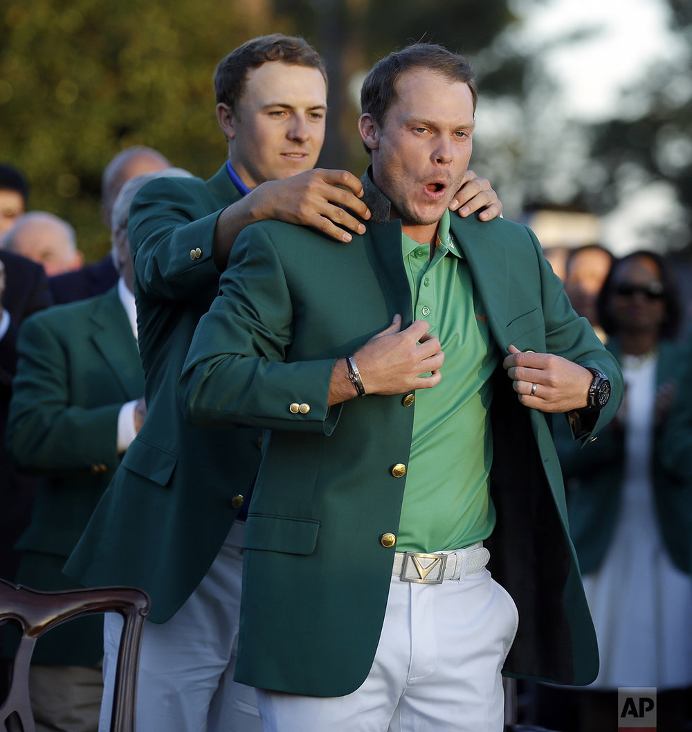 Defending champion Jordan Spieth, left, helps 2016 Masters champion Danny Willett, of England, put on his green jacket following the final round of the Masters golf tournament on April 10, 2016, in Augusta, Ga. (AP Photo/Chris Carlson)