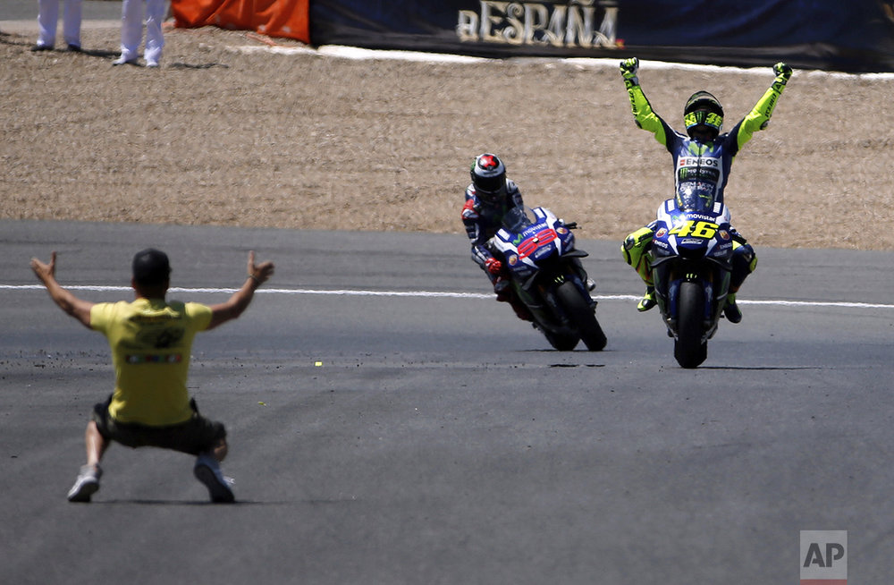 Moto GP rider Valentino Rossi of Italy, right, celebrates after winning the MotoGP race of Spain's Motorcycle Grand Prix at the Jerez race track in Jerez de la Frontera, southern Spain, on April 24, 2016. In the background is Jorge Lorenzo of Spain who finished second. (AP Photo/Miguel Angel Morenatti)