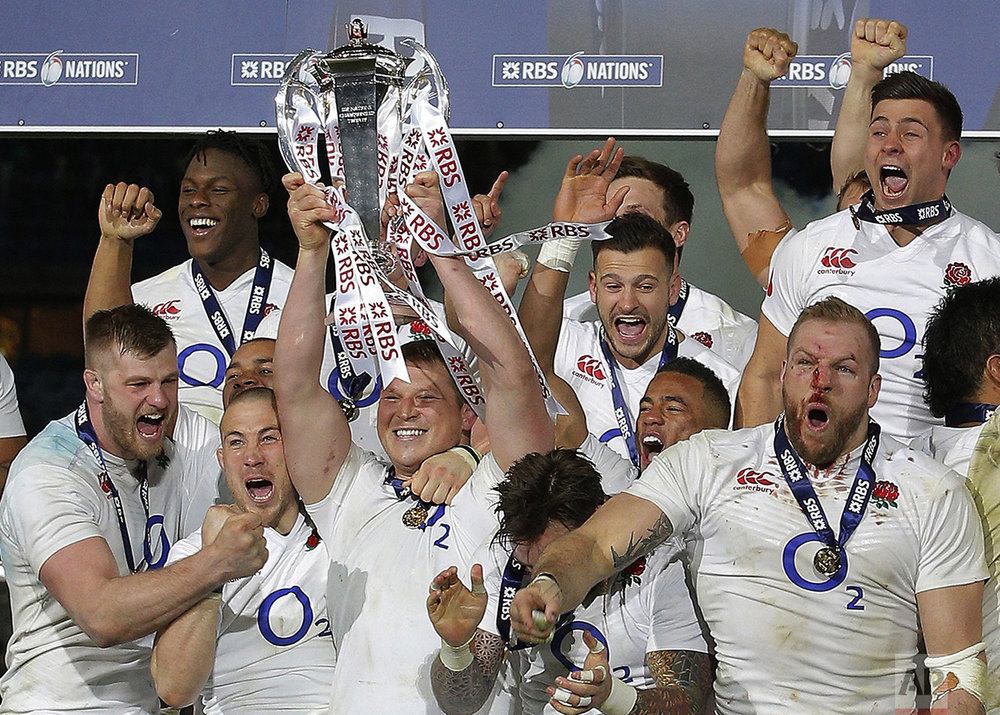 England's Dylan Hartley holds the trophy aloft as he celebrates with teammates after the Six Nations international rugby match between France and England at the Stade de France stadium in Saint-Denis, outside Paris, on March 19, 2016. England won the game to clinch the Grand Slam. (AP Photo/Christophe Ena)