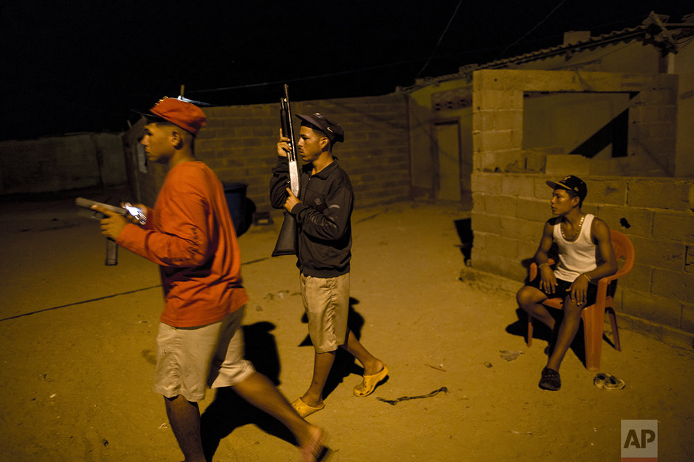 "In this Nov. 2, 2016 photo, members of the Marval family, who patrol at night while other members of their family fish at sea, respond to what appeared to be the start of an attack by pirate gang leader ""El Beta"" in Punta de Araya, Sucre state, Venezuela. The family says El Beta is a 19-year-old killer with 40 men at his command who threatened to kill their entire clan days after murdering three Marvals at sea and stealing their night's catch. (AP Photo/Rodrigo Abd)"