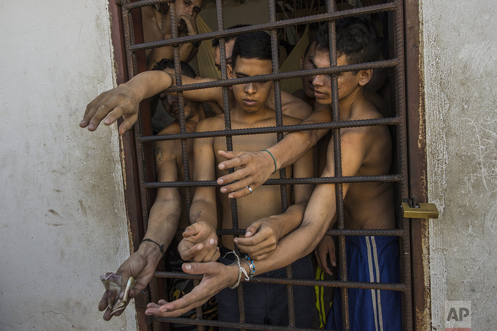 In this Nov. 7, 2016 photo, suspects of violent crimes ask police for food, as one holds out money, from inside a holding cell at the municipal police station in Cumana, Sucre state, Venezuela. While police provide food, prisoners get most of their food and drinks from their families. (AP Photo/Rodrigo Abd)