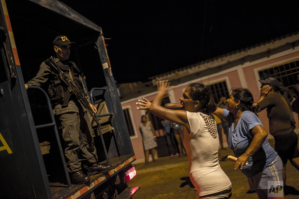 In this Nov. 10, 2016 photo, women argue with a National Guard, saying they've detained the wrong men while cracking down on pirates in Punta de Araya, Sucre state, Venezuela. After villagers protested they knew their suspects to be honest fishermen, the soldiers let the three men go. (AP Photo/Rodrigo Abd)
