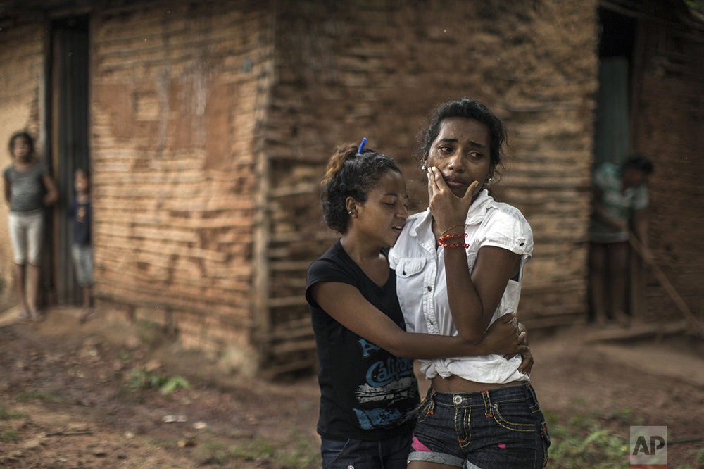 In this Nov. 12, 2016 photo, Mariela Cabello, right, grieves after her brother was killed along with eight other villagers in Cariaco, Sucre state, Venezuela. Five law enforcement officers were charged with storming the village and killing nine men from a fishing family, who were widely thought to have belonged to a gang. (AP Photo/Rodrigo Abd)