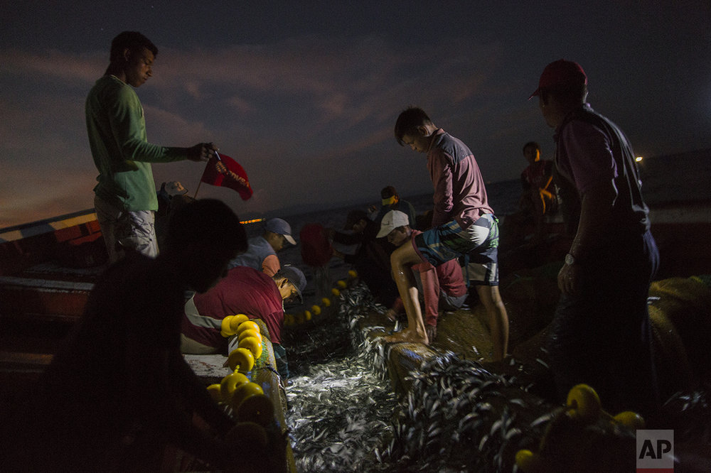 "In this Oct. 31, 2016 photo, the Marval family fish at night in the sea, off Punta de Araya, Sucre state, Venezuela. Sucre was the epicenter of food riots that swept through the country in June, and Punta de Araya families got through the summer by eating ""dog soup,"" a broth made from seawater and the small fish that are usually thrown back. (AP Photo/Rodrigo Abd)"