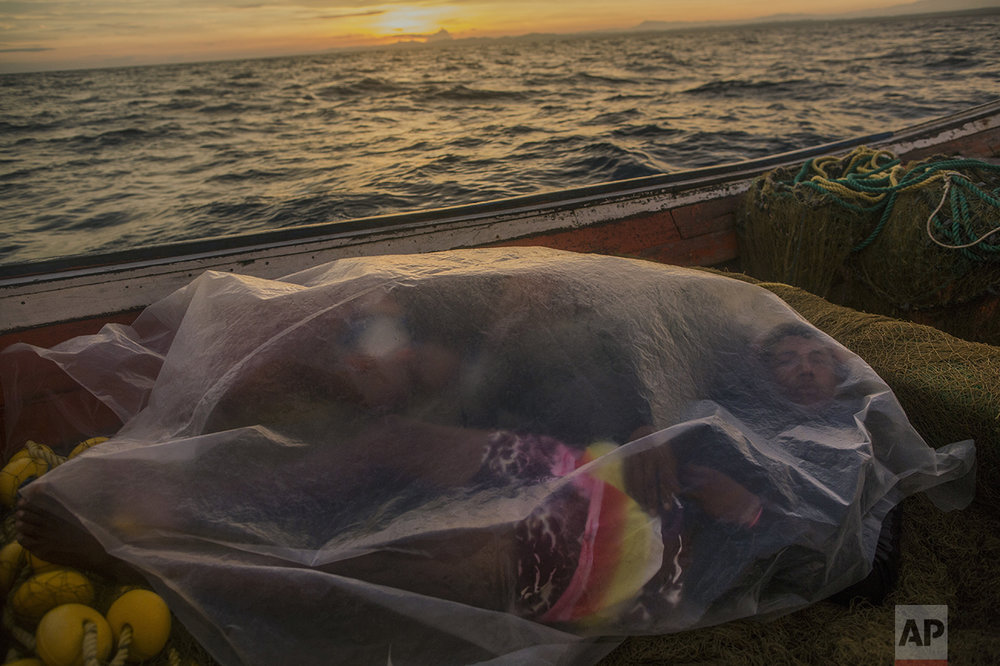 In this Nov. 8, 2016 photo, Jorge Marval naps in his boat under a plastic sheet after fishing all night, as the sun rises off Punta de Araya, Sucre state, Venezuela. The fishing trade has collapsed, along with virtually every industry across Venezuela. (AP Photo/Rodrigo Abd)