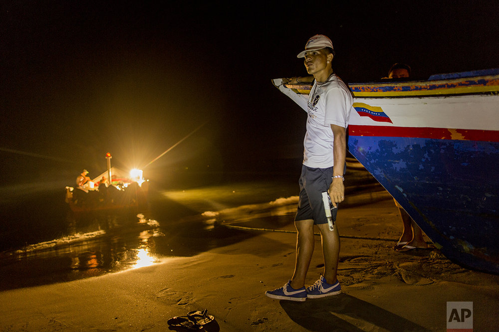 "In this Nov. 2, 2016 photo, a member of the Marval fishing family who goes by the nickname ""El Chukiti"" holds a homemade gun as he guards against a possible pirate attack as fishermen unload their catch in Punta de Araya, Sucre state, Venezuela. The family's self-defense group calls themselves ""Los Cainos."" (AP Photo/Rodrigo Abd)"