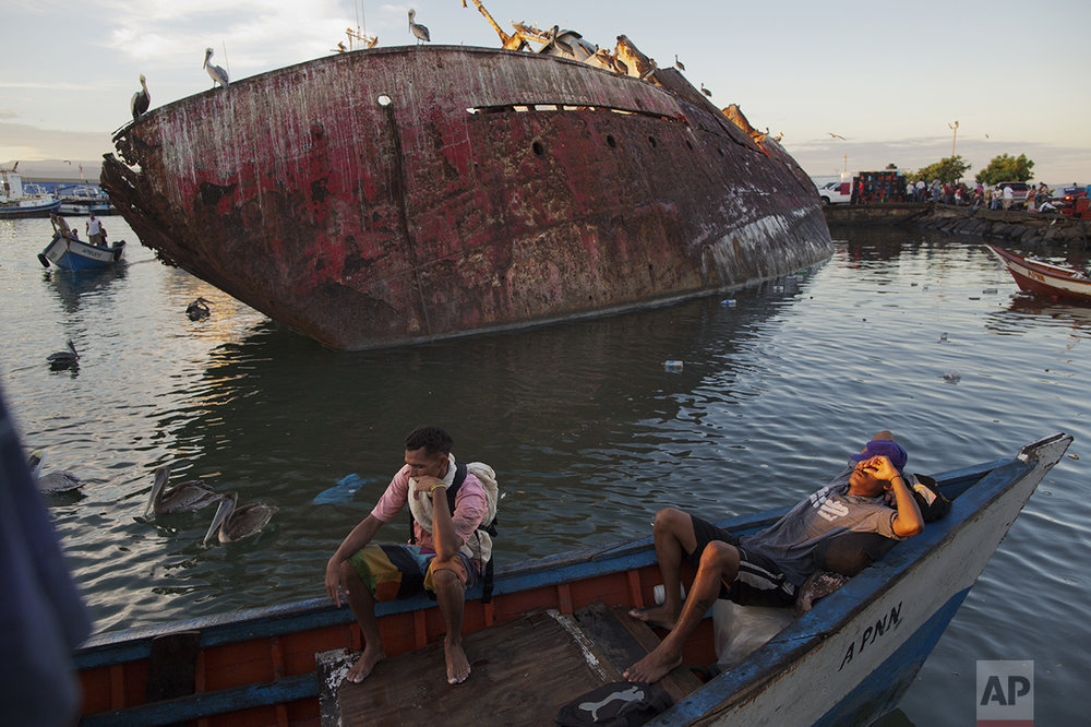 In this Nov. 30, 2016 photo, fishermen rest after selling their catch at the fish market in the port of Cumana, Sucre state, Venezuela. Here on the coast, the tuna catch is down to less than a third of the 120,000 tons Venezuela produced in 2004. (AP Photo/Rodrigo Abd)