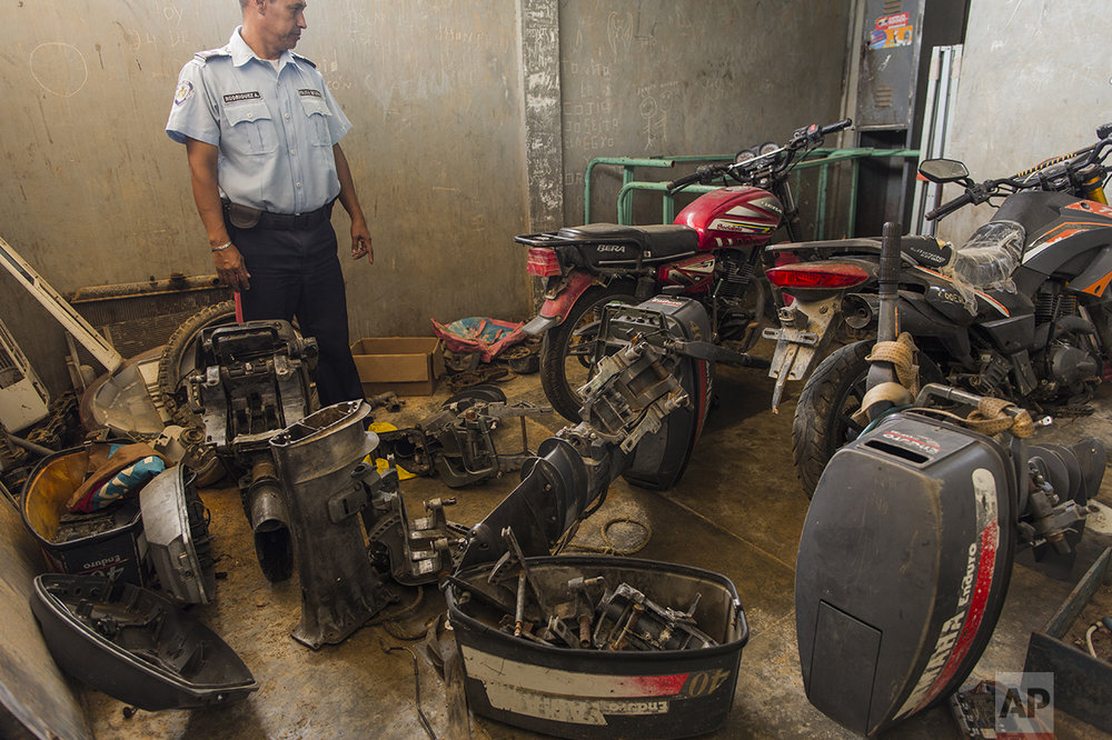 """In this Nov. 11, 2016 photo, a municipal police officer stands amid stolen engines seized from pirates, at the police station in Punta de Araya, Sucre state, Venezuela. """"People can't make a living fishing anymore, so they're using their boats for the options that are left: smuggling gas, running drugs, and piracy,"""" said Jose Antonio Garcia, leader of the state's largest union. (AP Photo/Rodrigo Abd)"""