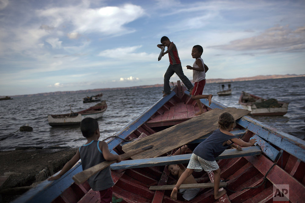 "In this Nov. 9, 2016 photo, children play ""pirates"" on a fishing boat in Cumana, Sucre state, Venezuela. ""You hear piracy and you think of guys robbing container ships in Africa. But here it's just poor fishermen robbing other poor fishermen,"" said Sucre lawyer Luis Morales. ""It's the same kind of crime we've seen in the streets, but spreading to the sea. (AP Photo/Rodrigo Abd)"