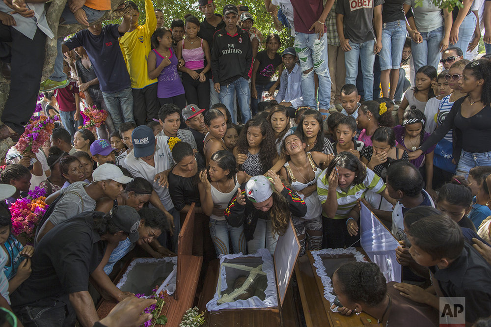 In this Nov. 13, 2016 photo, relatives of nine men from a fishing family, who were shot in the head while on their knees, mourn them at the cemetery in Cariaco, Sucre state, Venezuela. Five law enforcement officers were charged with storming the village and killing these men, who were widely thought to have belonged to a gang. (AP Photo/Rodrigo Abd)