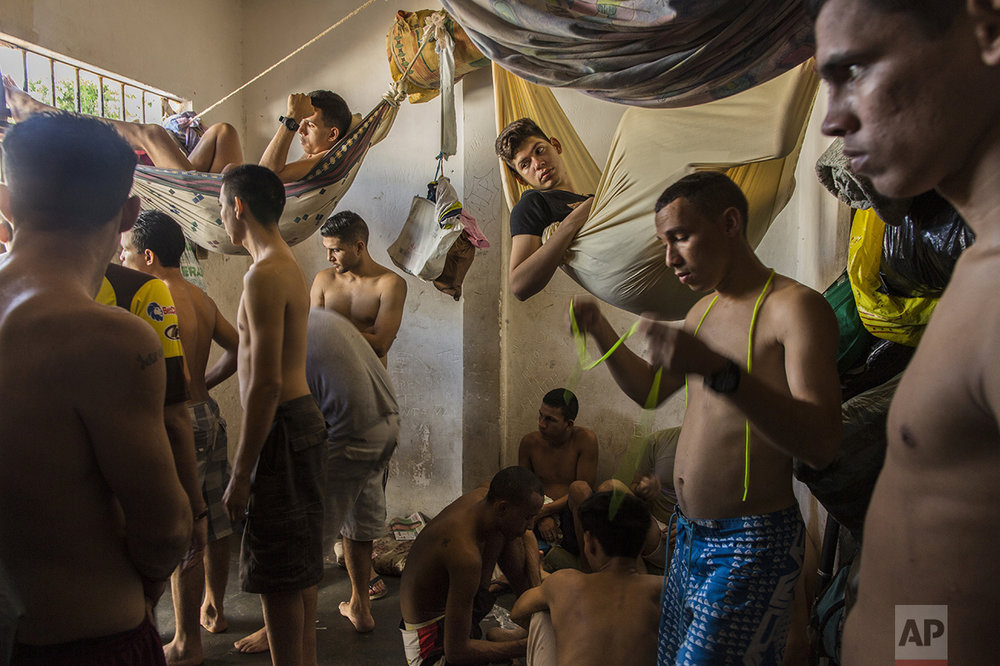 In this Nov. 7, 2016 photo, suspects of violent crime crowd a holding cell at the municipal police station in Cumana, Sucre state, Venezuela. Police are reluctant to make mass arrests of pirates robbing and killing fishermen at sea because the jails are already packed full, with prisoners sleeping in shifts at night. (AP Photo/Rodrigo Abd)