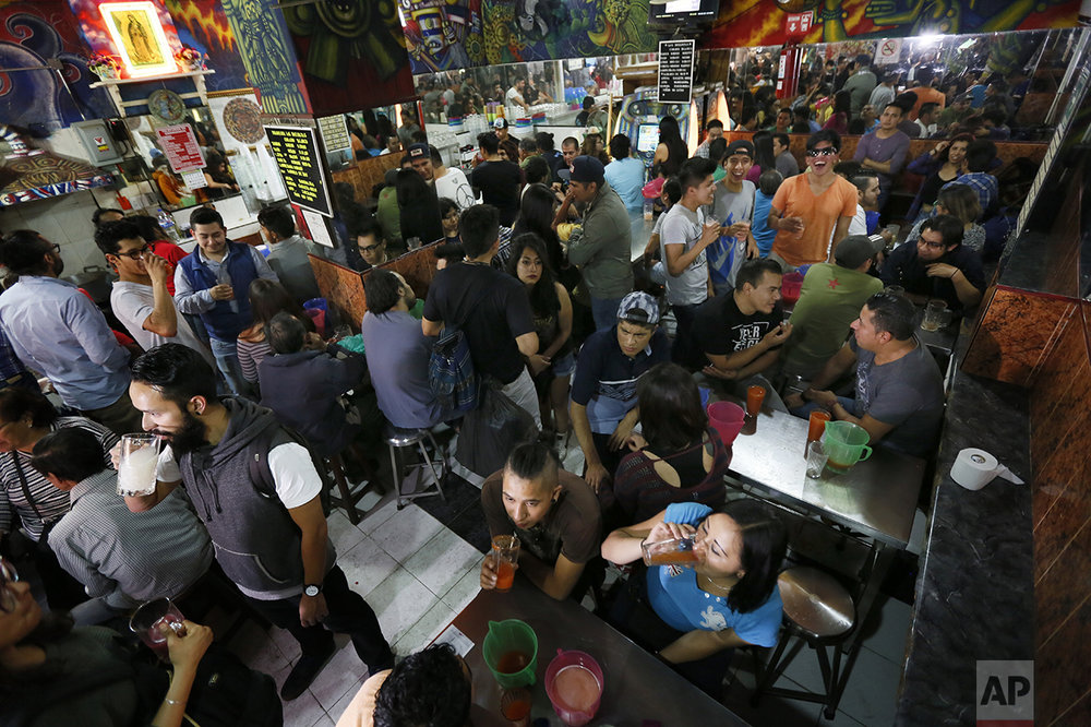 This Dec. 3, 2016 photo shows the pulqueria Las Duelistas overflowing with patrons, in Mexico City. Mexicans have been brewing pulque from the juice of cactus-like maguey plants for centuries, but the viscous, beer-like beverage fell out of favor starting in the 1970s as pulque got a bad reputation as a peasant's drink. The nutrient-rich drink is making a comeback among a new generation of Mexicans. (AP Photo/Marco Ugarte)
