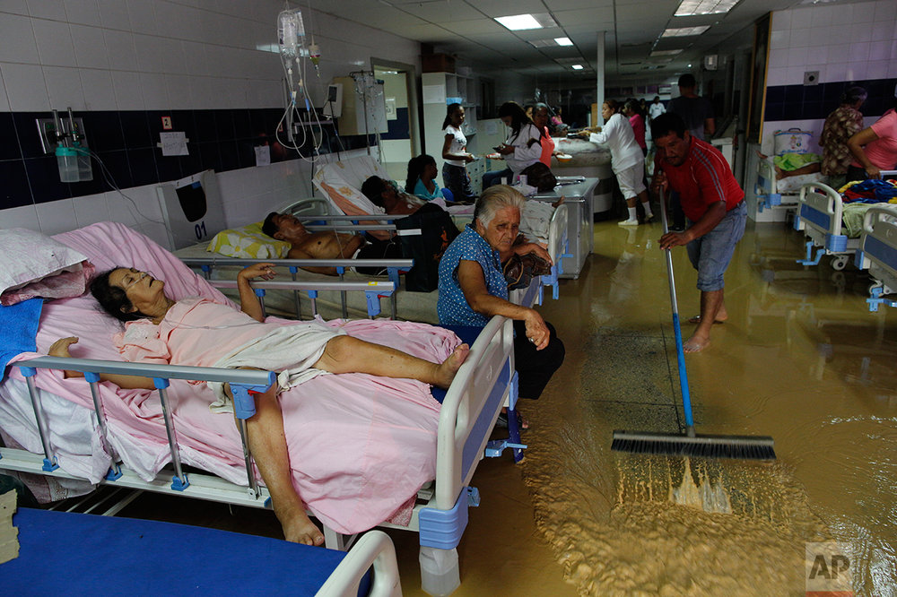 In this Nov. 3, 2016 photo, the relative of a public hospital patient pushes water out of the emergency room after flooding triggered by heavy rain in Cumana, Sucre state, Venezuela. The hospital lacks medicine and beds. Hygiene is so bad that some patients who come to the ER end up dying from bacterial infections caught there. (AP Photo/Rodrigo Abd)