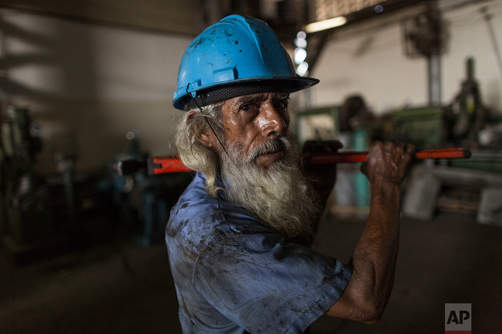 In this Oct. 29, 2016 photo, tuna ship mechanic Jose Noriega, 66, stops for a portrait as he works in the state run fishing company Pescalba, in Cumana, Sucre state, Venezuela. The government nationalized Pescalba in 2010. (AP Photo/Rodrigo Abd)