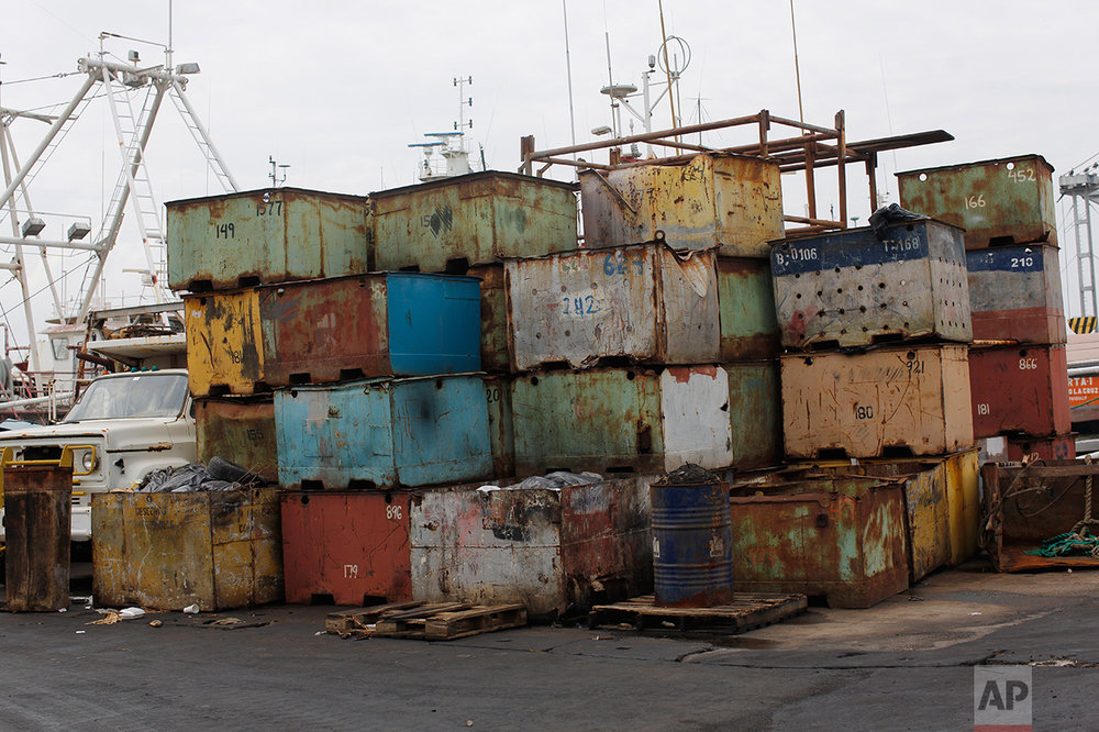 In this Nov. 4, 2016 photo, old fish containers are stored at the state-run fishing company Pescalba in Cumana, Sucre state, Venezuela. On a recent workday, more than half of the company's fleet bobbed uselessly at the dock, holes gaping where the ships' decks and sides had rusted open. (AP Photo/Rodrigo Abd)