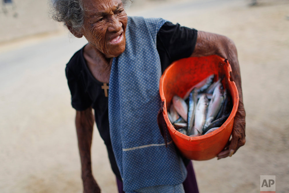 In this Nov. 14, 2016 photo, a woman carries a bucket of fish that her fishermen neighbors gave her as a gift as she returns home from work in Punta de Araya, Sucre state, Venezuela. When times are hard, Venezuela's capital city gets the lion's share of resources and the provinces get less than ever. (AP Photo/Rodrigo Abd)