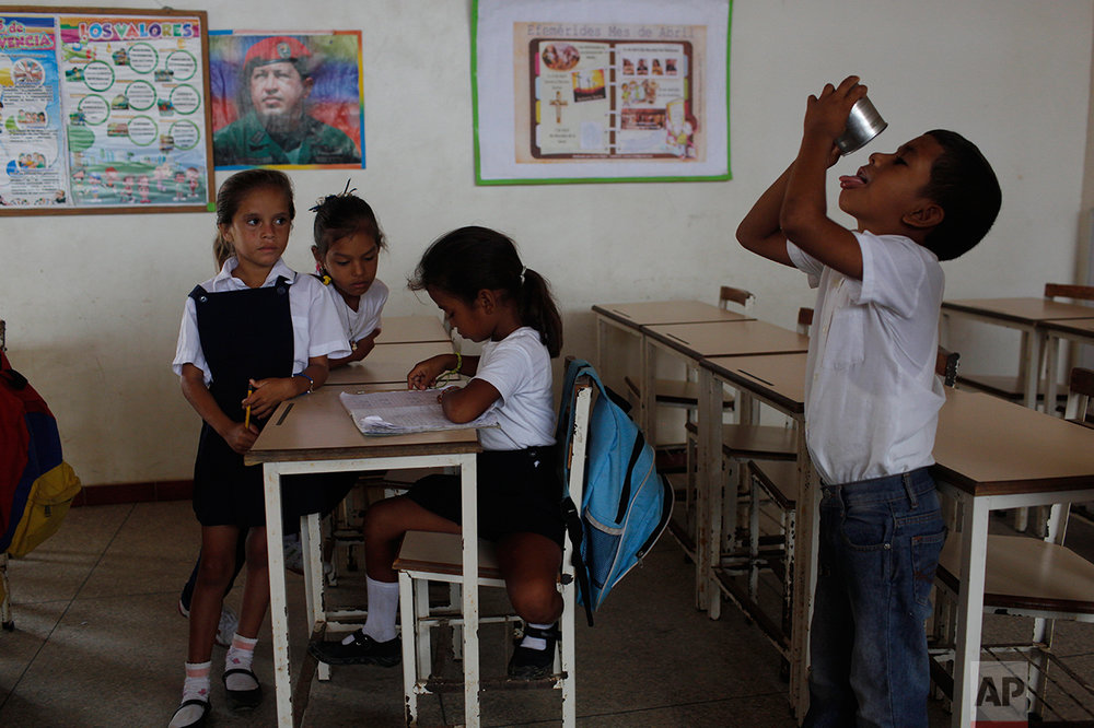 In this Nov. 8, 2016 photo, a boy finishes his breakfast inside a classroom at the public school in Punta de Araya, Sucre state, Venezuela. The schedules at state schools are determined by whether or not there is food for students, and many times classes are suspended due to lack of drinking water. (AP Photo/Rodrigo Abd)