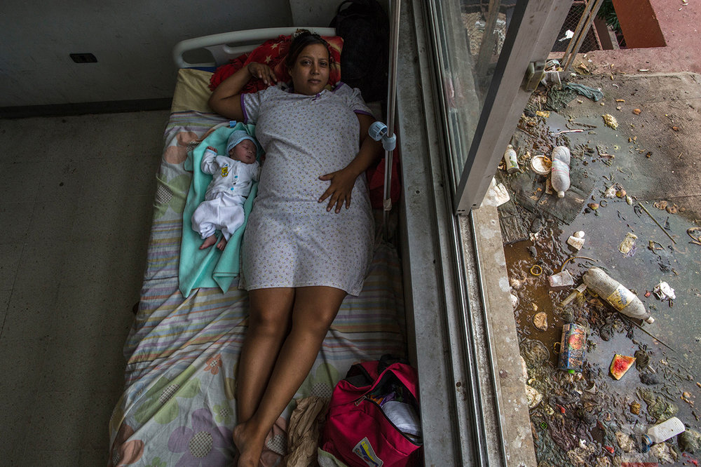 In this Nov. 5, 2016 photo, Virginia Vargas rests with her 1-day-old baby in the maternity ward at the public hospital in Cumana, Sucre state, Venezuela. According to obstetrician Javier Vegas, his hospital lacks basic supplies, so doctors have to wash and reuse materials like sutures, and many new mothers get infections as a result. (AP Photo/Rodrigo Abd)