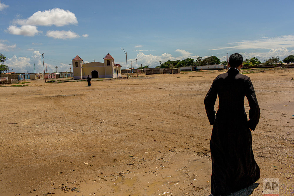 In this Nov. 6, 2016 photo, a priest walks to the chapel in Punta de Araya, Sucre state, Venezuela. The local church is trying to mediate between rival gangs in the area. (AP Photo/Rodrigo Abd)
