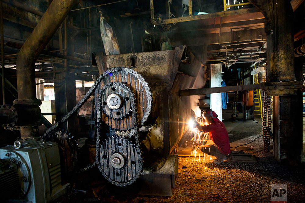 """In this Nov. 3, 2016 photo, a worker repairs machinery to get it ready for the next sugar cane harvest at a sugar mill in Cumanacoa, Sucre state, Venezuela. """"We are revolutionaries, but in this factory there are no letters of credit, no spare parts for the machines, so we do what we can to keep it going,"""" said welder Jose Armando Bastardo. (AP Photo/Rodrigo Abd)"""