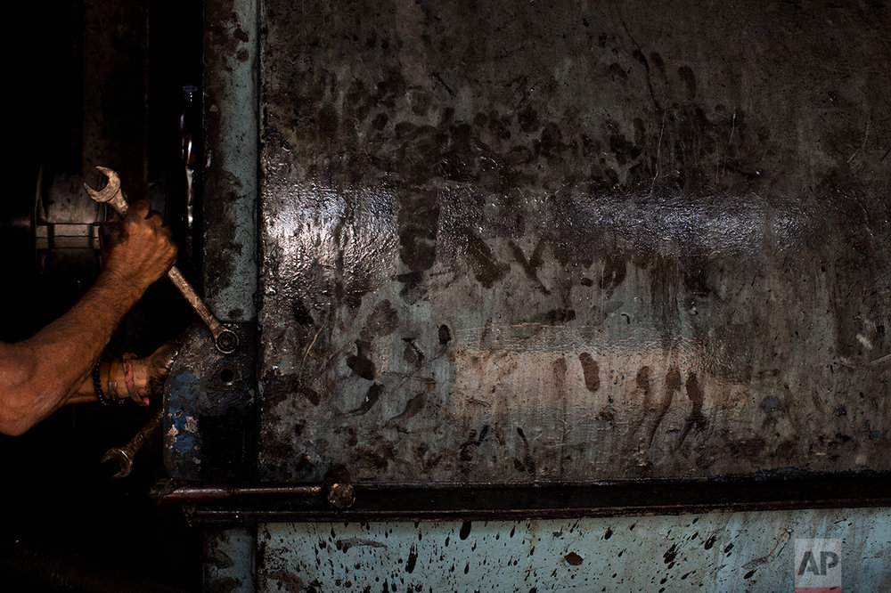 In this Nov. 3, 2016 photo, a worker repairs machinery to get it ready for the next sugar cane harvest at a sugar mill in Cumanacoa, Sucre state, Venezuela. The sugar and fish processing plants work at half capacity on good days. (AP Photo/Rodrigo Abd)