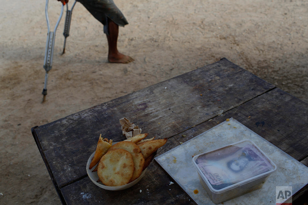 """This Nov. 2, 2016 photo shows cash earned by a street vendor selling """"empanadas"""" on a table in Punta de Araya, Sucre state, Venezuela. In the nation's capital, people bang pots at nightfall to protest the country's economic ruin, doctors shut down hospitals in protest, and students march on government buildings to demand relief. But the collapse has been far more savage in the rest of the country, and far less visible. (AP Photo/Rodrigo Abd)"""