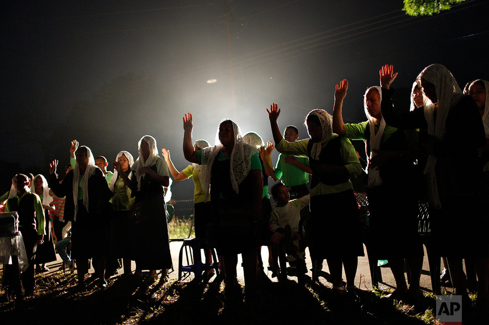 """In this Nov. 12, 2016, members of the evangelical church """"La Nueva Jerusalen"""" pray in Cariaco, Sucre state, Venezuela. One civil engineer from Caracas said he moved here two decades ago for a more peaceful life. As the state sinks deeper into chaos, he's thinking of moving back. Caracas is a lifeboat, he said, and the rest of the country is quietly drowning. (AP Photo/Rodrigo Abd)"""