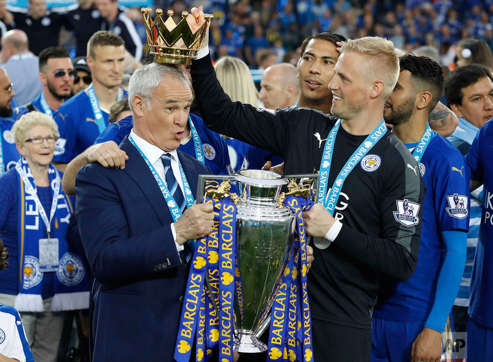 In this Saturday, May 7, 2016 photo, Leicester City team manager Claudio Ranieri has the crown of the trophy placed on his head by Leicester goalkeeper Kasper Schmeichel as they celebrate becoming the English Premier League soccer champions at King Power stadium in Leicester, England The preseason 5,000-1 title longshots swept the big spending teams aside to win biggest prize in English football Saturday. (AP Photo/Matt Dunham)
