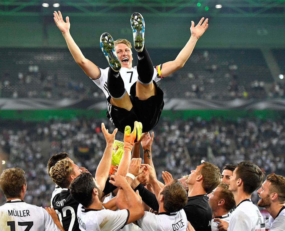 In this Wednesday, Aug. 31, 2016 photo, Germany's national soccer team throws their captain Bastian Schweinsteiger into the air after he played his last match for the national team in Moenchengladbach, Germany. (AP Photo/Martin Meissner)