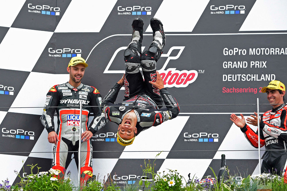 In this Sunday, July 17, 2016 photo, second placed driver Jonas Folger, left, from Germany and third placed Julian Simon, right, from Spain look on as first placed Moto 2 driver Johann Zarco, center, from France performs a backflip during the award ceremony for the Moto2 race on the Sachsenring in Hohenstein-Ernstthal, Germany. (AP Photo/Jens Meyer)
