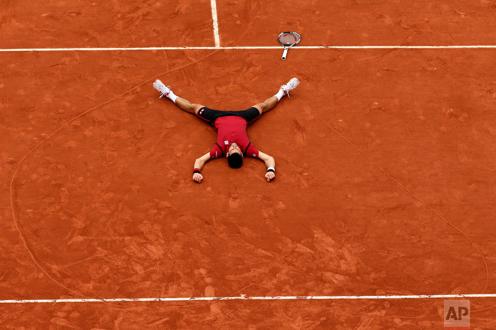 In this Sunday, June 5, 2016 photo, Serbia's Novak Djokovic lays on the clay in a heart in drew after defeating Britain's Andy Murray during their final match of the French Open tennis tournament at the Roland Garros stadium in Paris. Djokovic won 3-6, 6-1, 6-2, 6-4. (AP Photo/David Vincent)