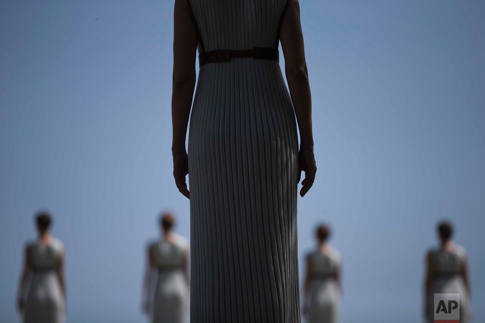 In this Wednesday, April 20, 2016 photo, High Priestess Katerina Lehou stands in front of a line of priestesses during the dress rehearsal for the lighting of the Rio Olympics flame, in Ancient Olympia, southern Greece. The meticulously choreographed ceremony will be repeated Thursday in the ruined birthplace of the ancient Olympics in southern Greece, in the presence of top International Olympic Committee and Rio organizing officials. (AP Photo/Petros Giannakouris)