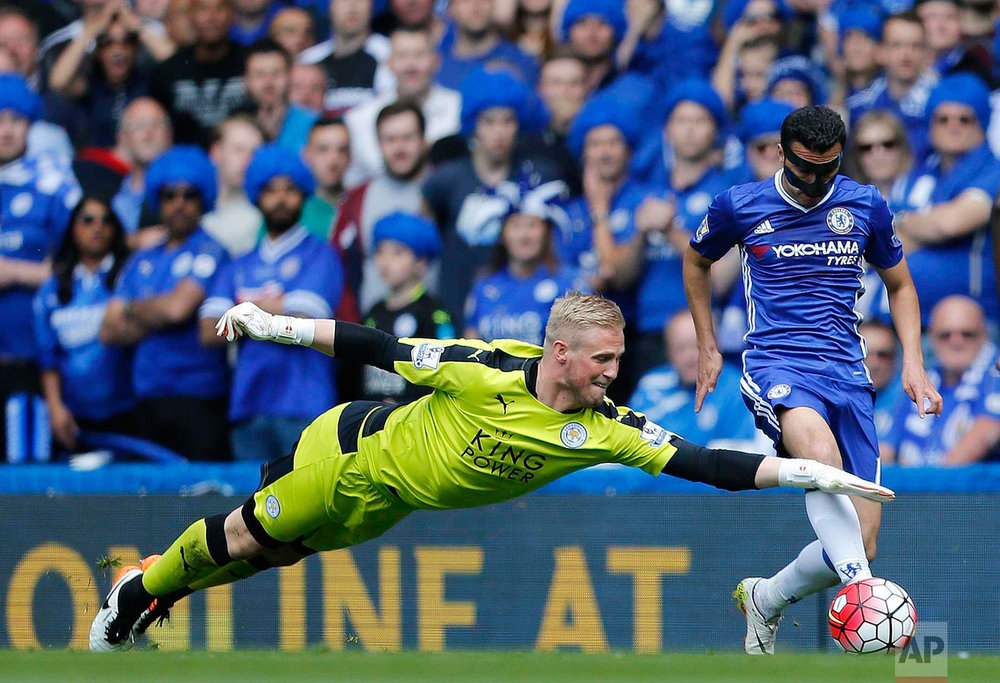 In this Sunday, May 15, 2016 photo, Leicester's goalkeeper Kasper Schmeichel, left, and Chelsea's Pedro challenge for the ball during the English Premier League soccer match between Chelsea and Leicester City at Stamford Bridge stadium in London. (AP Photo/Frank Augstein)