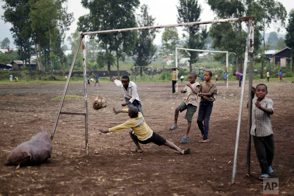 In this Saturday June 18, 2016 photo, Congolese children play soccer on a dirt field in Goma, Democratic Republic of Congo. One goal was scored with the old deflated ball the children use to play with. (AP Photo/Jerome Delay)