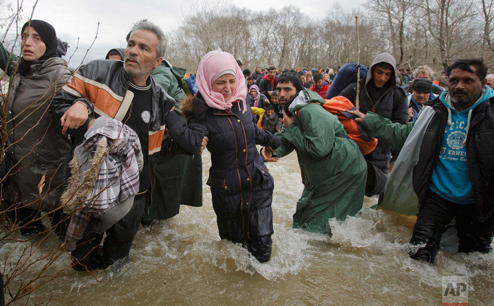 In this March 14, 2016 photo, a woman cries as she crosses the river along with other migrants, north of Idomeni, Greece, attempting to reach Macedonia on a route that would bypass the border fence. (AP Photo/Vadim Ghirda)