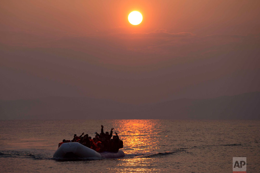In this March 20, 2016 photo, the sun rises as migrants and refugees on a dingy arrive at the shore of the northeastern Greek island of Lesbos, after crossing the Aegean sea from Turkey (AP Photo/Petros Giannakouris)