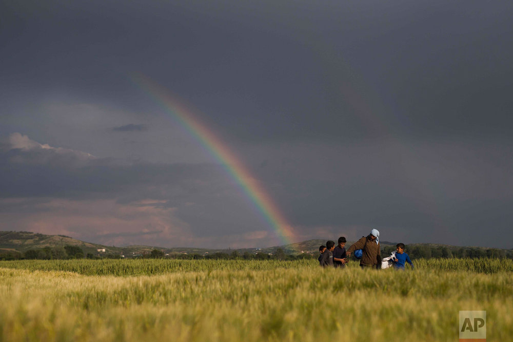 In this Saturday, May 7, 2016 photo, Syrian refugees walk on fields in front of a rainbow at the northern Greek border point of Idomeni, Greece. Thousands of migrants and refugees are trapped in Idomeni for months unable to continue their trip to Europe as the border remain closed. (AP Photo/Petros Giannakouris)