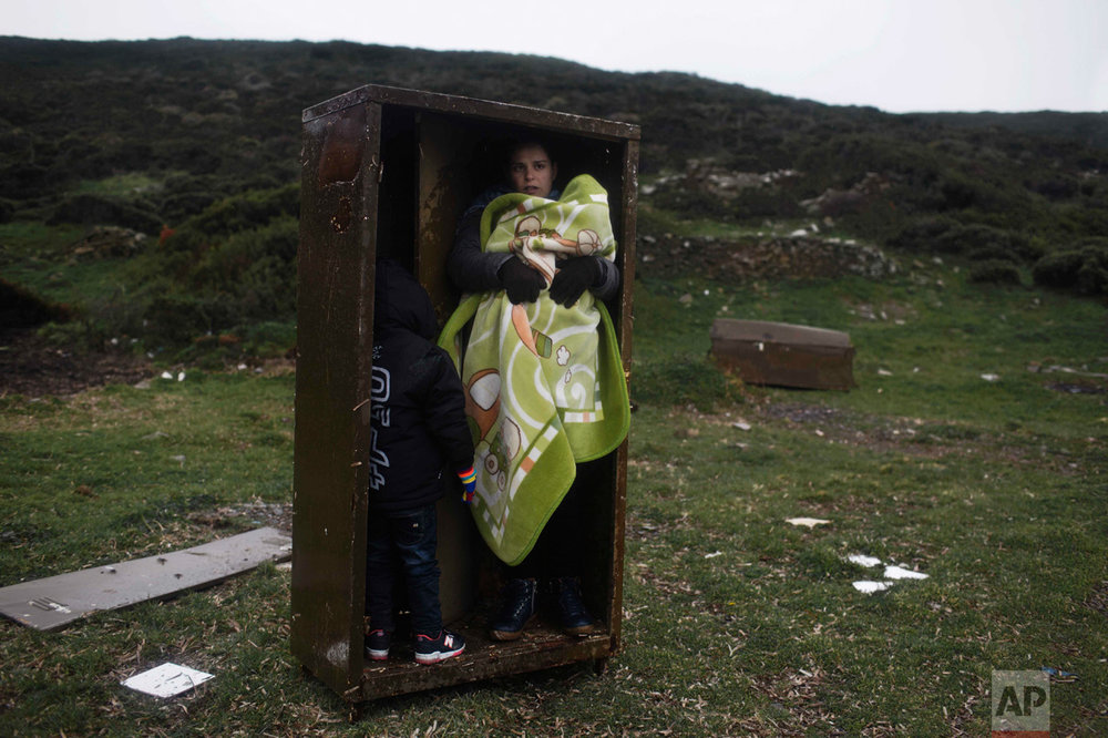 In this Wednesday, Jan. 20, 2016 photo, a Syrian woman with her children takes a shelter in a iron box during a rainfall after they arrived from Turkey to the Greek deserted island of Pasas near Chios. Europe's biggest migration crisis since the end of World War II saw more than a million people flee war and poverty arrived in financially struggling Greece. (AP Photo/Petros Giannakouris)