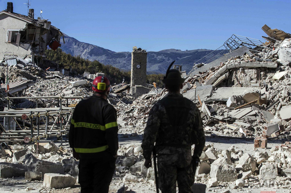 A firefighter, left, and an alpine soldier look at rubble in the hilltop town of Amatrice after an earthquake with a preliminary magnitude of 6.6 struck central Italy on Oct. 30, 2016. The powerful earthquake rocked the same area of central and southern Italy hit by a quake in August, and a pair of aftershocks just a week prior to this one sent already quake-damaged buildings crumbling after a week of temblors that have left thousands homeless. (Massimo Percossi/ANSA via AP)