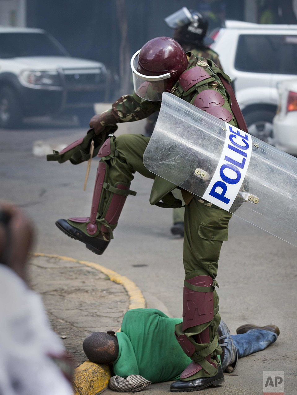 In this Monday, May 16, 2016 photo, a Kenyan riot policeman repeatedly kicks a protester as he lies in the street after tripping over while trying to flee from them, during a protest in downtown Nairobi, Kenya. Kenyan police have tear-gassed and beaten opposition supporters during a protest demanding the disbandment of the electoral authority over alleged bias and corruption. (AP Photo/Ben Curtis)