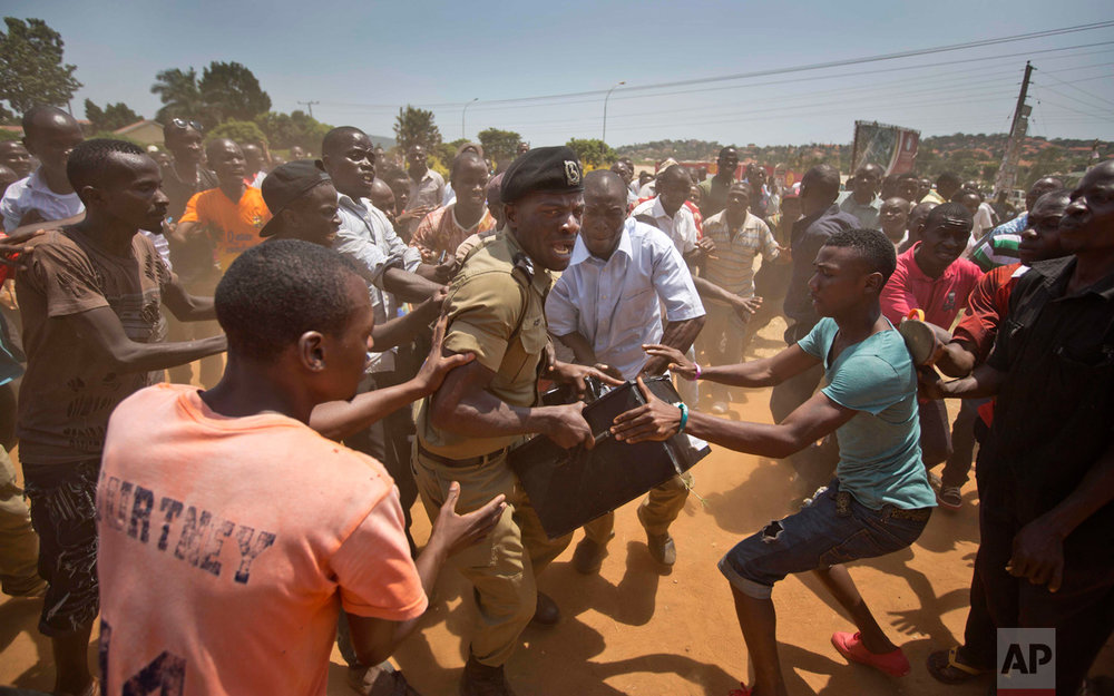 In this Thursday, Feb. 18, 2016 photo, a Ugandan policeman struggles to keep hold of a box containing voting material, as excited voters surround him after waiting over 7 hours without being able to vote, at a polling station in Ggaba, on the outskirts of Kampala, in Uganda. (AP Photo/Ben Curtis)